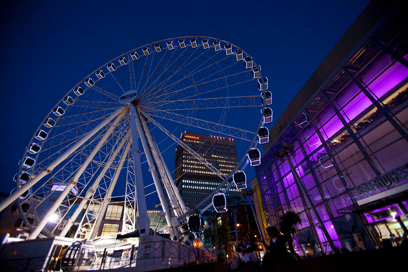 a Ferris wheel and buildings at night in England