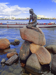a statue on the water's edge in Copenhagen