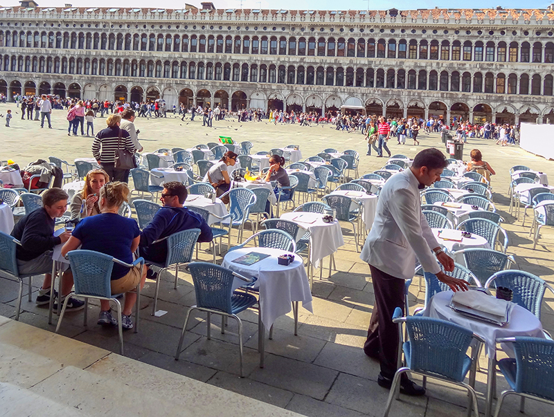 cafe tables in a large square in Venice, Italy