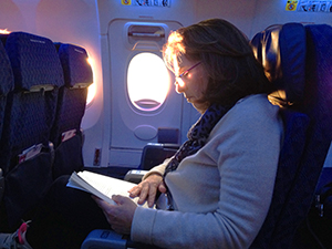 a woman reading a book on a plane
