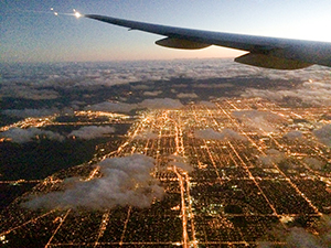 flying over a city at night - how to find cheap flights anywhere