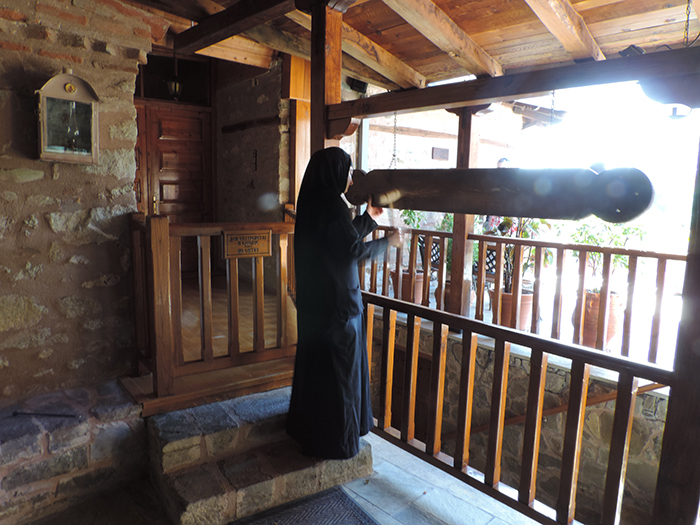 a nun standing by a railing in Meteora