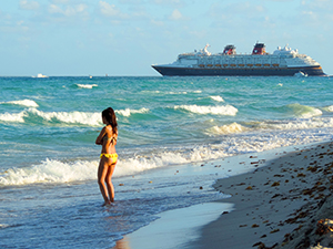 a woman on teh beach watchign an ocea liner deprt in South Beach Miami
