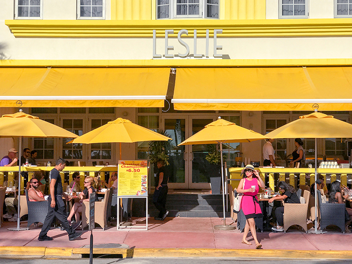 a woman in a red dress standing in front of a yellow building in South Beach Miami