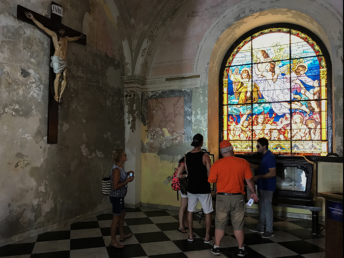 people looking at stained-glass windows in a cathedral