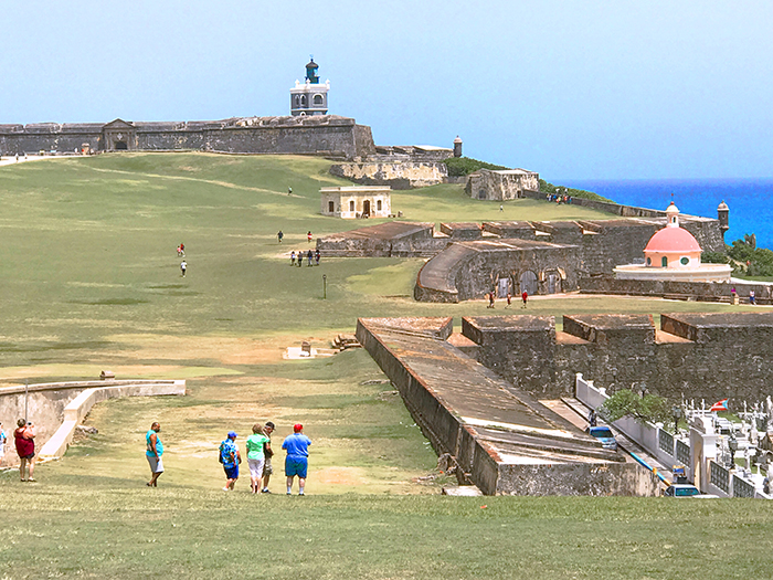 people on a large field by an old fort - one of the things to do in Puerto Rico San Juan