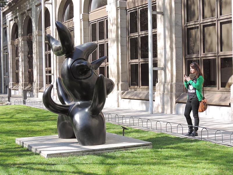 a woman in a sculpture garden