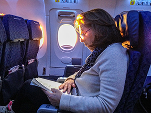 woman on a plane Budget Travel Tips