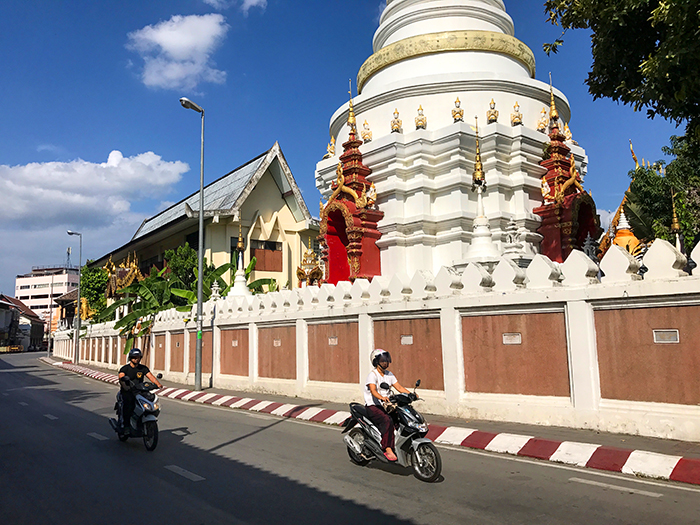 motorscooters passin a temple in Chiang Mai