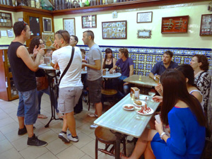 people sitting at tables in a bodega