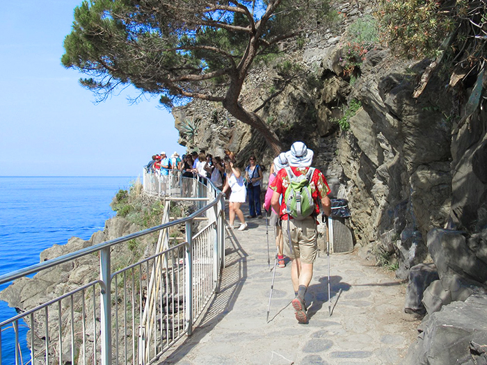people walking on a clifsside trail in Cinque Terre Italy