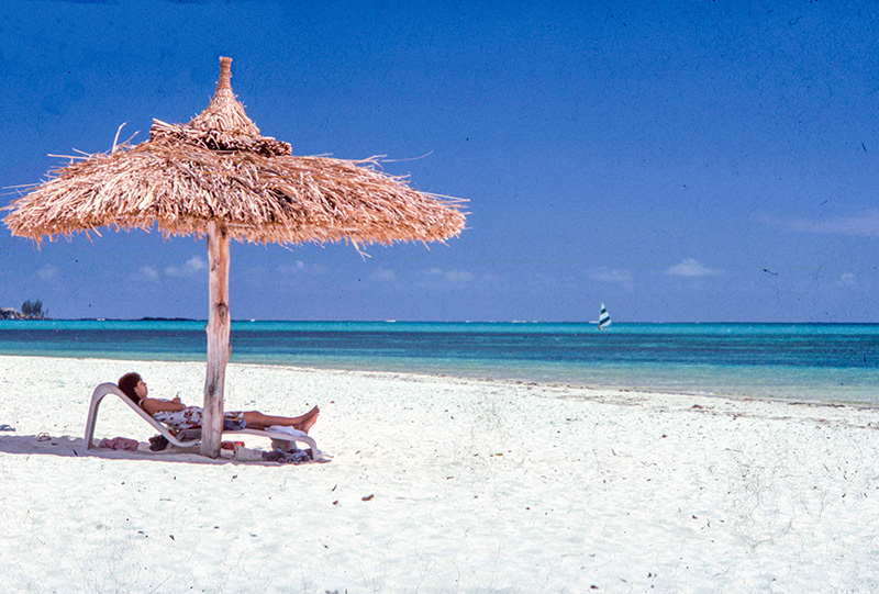 a women relaxing on a beach - travel insurance