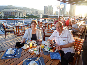 a couple eating a meal on the deck during a Pacific cruise