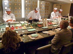 Sushi chefs with patrons