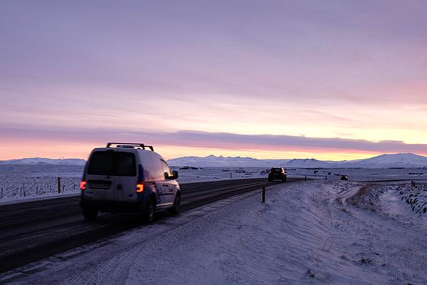 cars on road at sunrise - Iceland ice caves