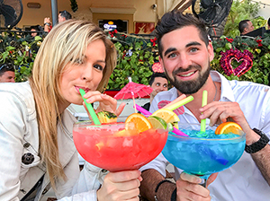 two young people with huge colorful cocktails