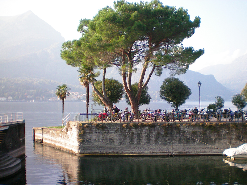 people sitting under a tree on the shore of Lake Como, one of the best places to visit in Italy