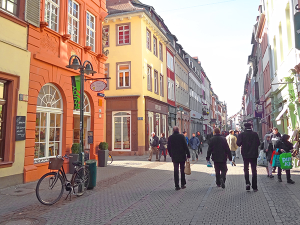 people waling past colorful old buildings