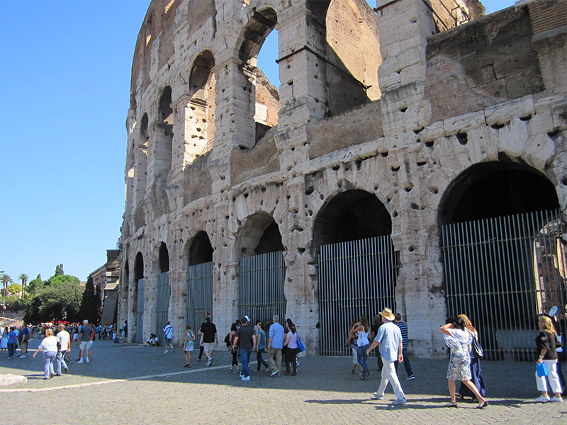 people walking outside Rome's Colosseum, one of the top places to visit in Italy