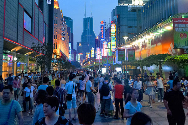 people walking on a crowded shopping street, one of the best things to do in Shanghai