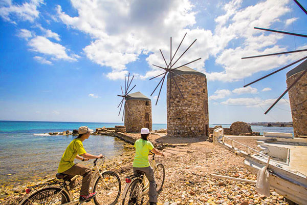 tourists on a Greece holiday looking at an old windmill