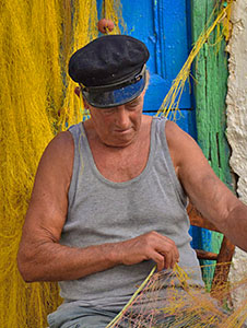 a fisherman tending his nets on Naxos, a good island for a Greece holiday