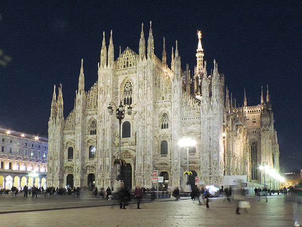 people viewing an ornate cathedral at night, one of the things to do in Milan