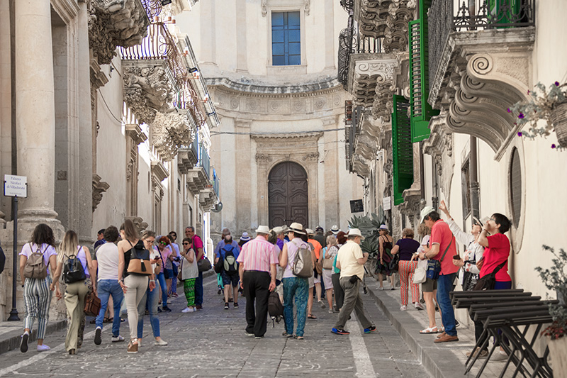 a tour group on a street - cities in Sicily