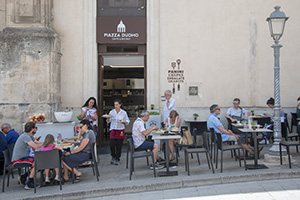 people in a cafe - cities in sicily
