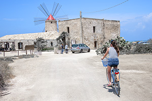 woman on a bicycle near a windmill - Mt. Etna