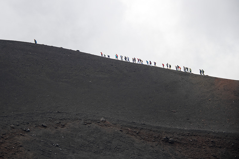 people walking along the rim of a volcano - palermo