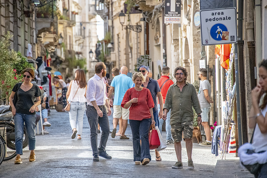 people on a street seen while touring Sicily by car