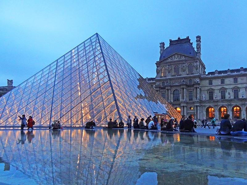 people seated by the glass pyramid of the Louvre, one of the places to visit during 2 days in Paris