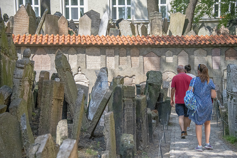 people walking through an old cemetary on a walking tour of Prague