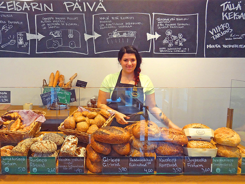A young woman with loaves of bread in a bakery