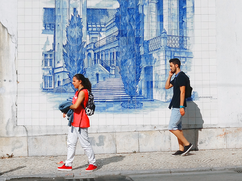 Image of two people walking past a tiled wall in Coimbra Portugal on a day trip from Lisbon