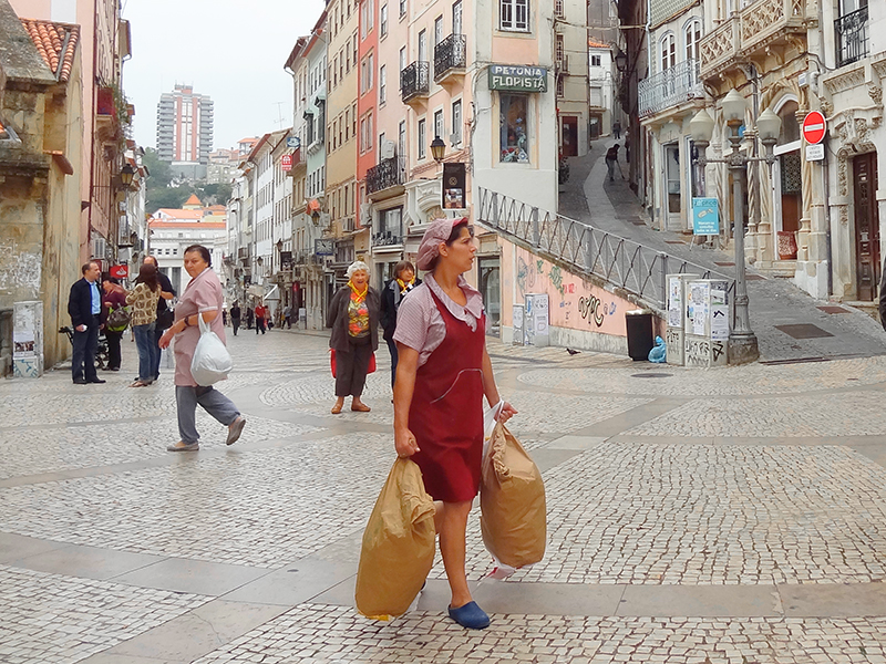 a woman walking on a street near the University of Coimbra seen on a day trip from Lisbon