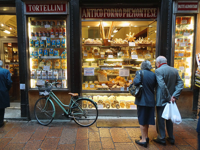 a couple looking at a window display of Bologna food