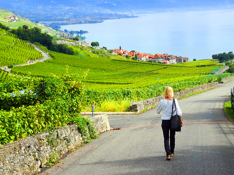 a woman walking through the Lavaux Vineyard terraces