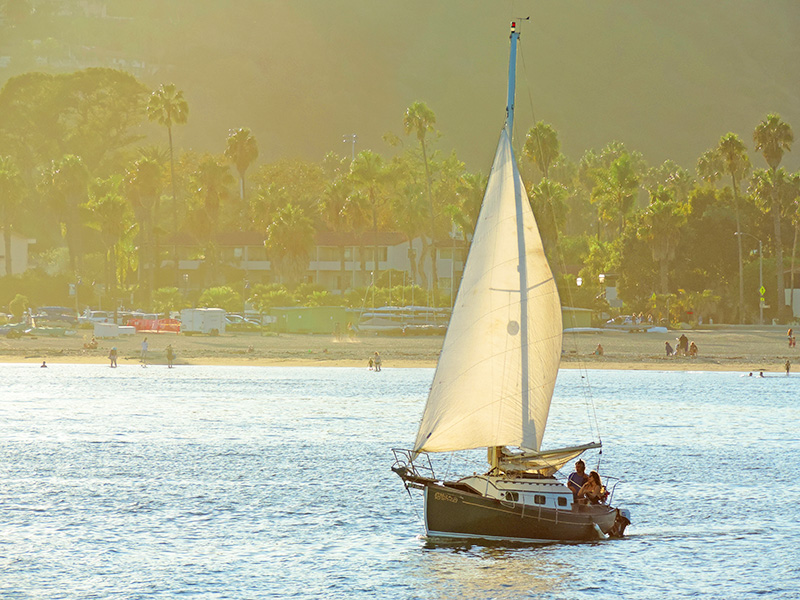 a couple sailing across teh narbor of the American Riviera