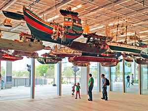 people in a museum with boats hanging from the ceiling - where to stay in Miami