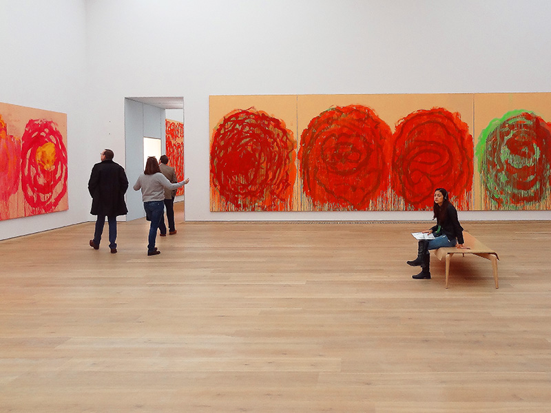 a woman sitting in a glallery in a modern art museum