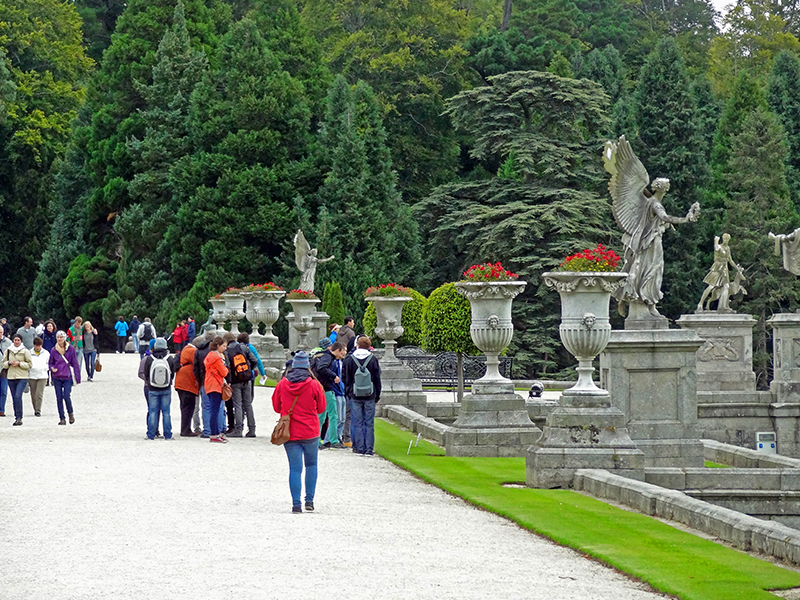 visitors walking by statuary on a lawn at Powerscourt, an ideal day trip from Dublin
