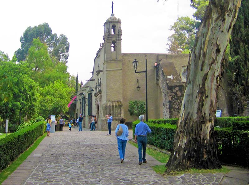 a couple walking towards a museum in a park