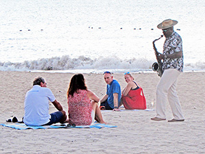man playing a saxophone on the beach at a luxxury St Lucia accommodation