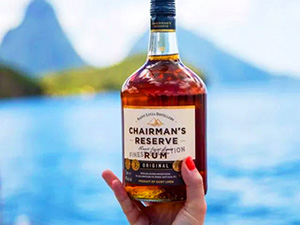 a hand holding a bottle of rum