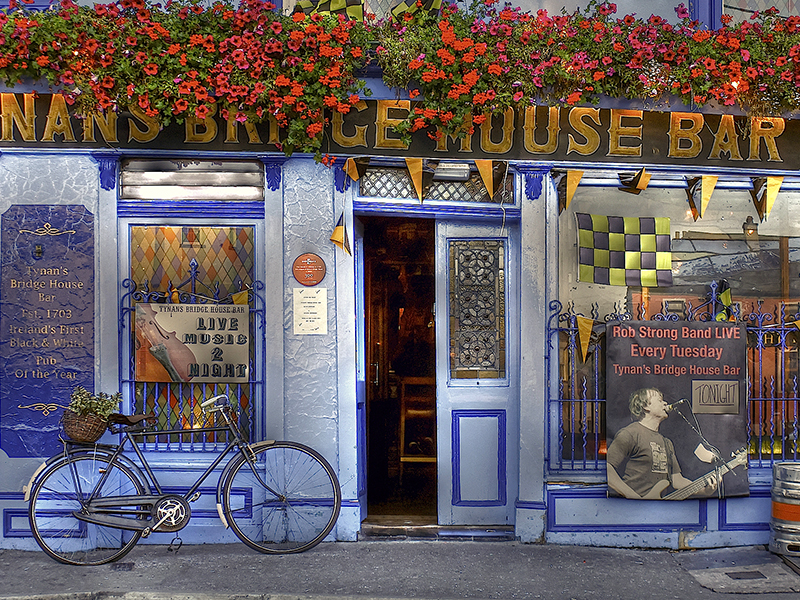 a bicycle in front of a bar painted blue in Kilkenny