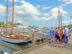 people on a dock awaiting a schooner in Camden, one of the popular towns on Maine Route 1