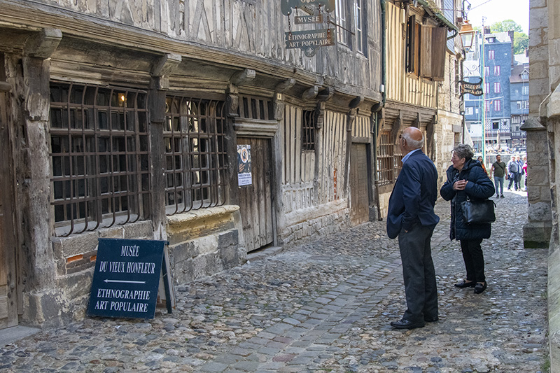 people looking at an old buillding seen on a trip to Normandy from Paris