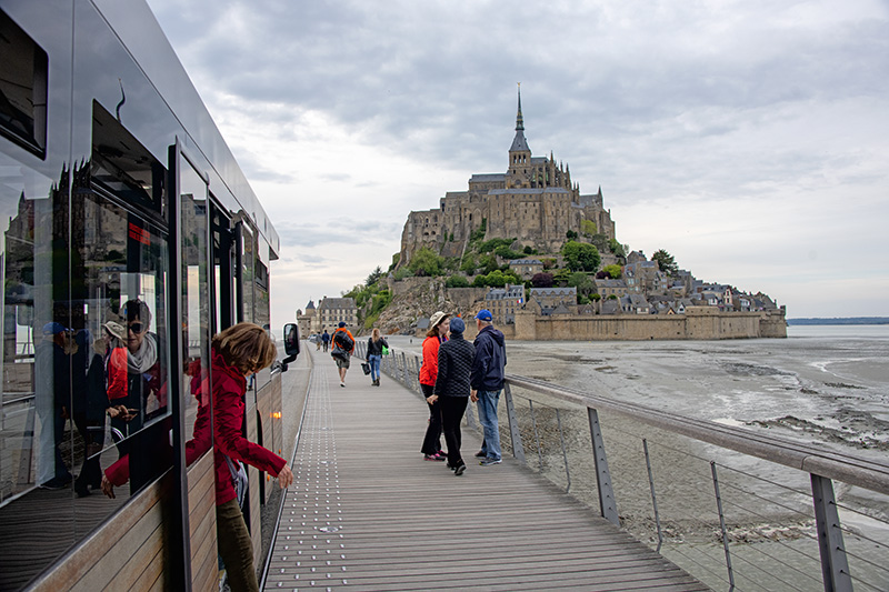 people on a causeway walking towards their Mont St. Michel hotel